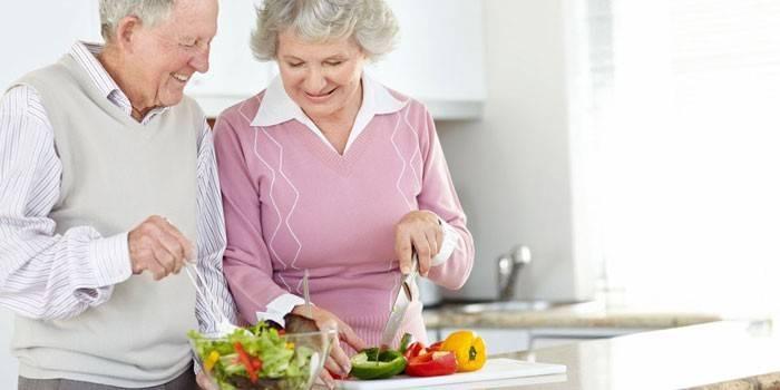 Пожилая пара готовить овощной салат