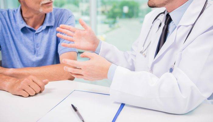 Male doctor talking with patient seriously at clinic. Close-up.