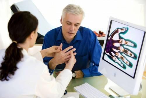 Врач осматривает кисть пациента